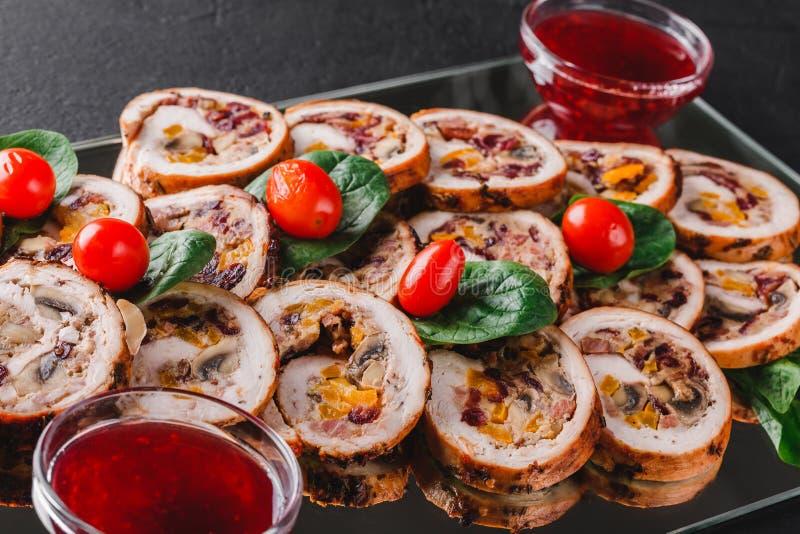 Sorterat kött, välfyllda fega rullar, köttrullar som stoppas med champinjoner, tranbär och torkade aprikors på bakgrund för svart arkivfoton