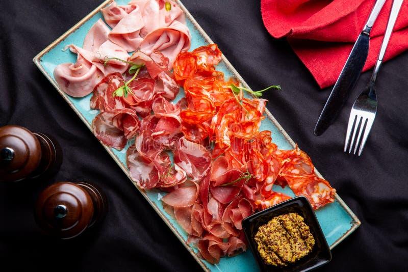 Sorterat kallt kött, prosciutto, skivar skinka, knyckigt för nötkött, salami, kött och senap på svart bakgrund Köttaptitretare royaltyfri foto
