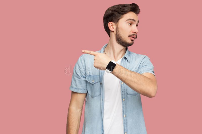 Sortez d'ici Portrait de jeune homme barbu beau f?ch? dans la chemise bleue de style occasionnel tenant et montrant la mani?re de photos libres de droits