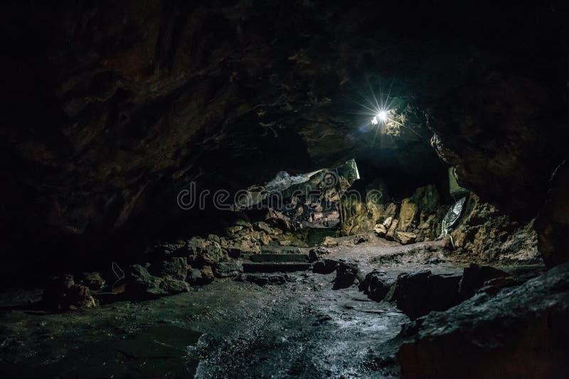 Sortez de la grande caverne souterraine effrayante foncée sous la forme de tunnel images stock