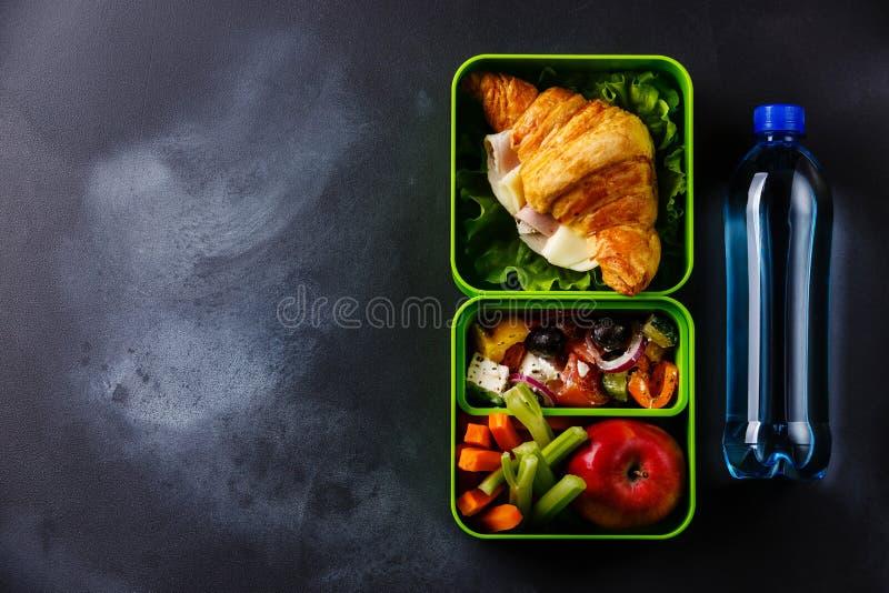 Sortez la gamelle de nourriture avec de l'eau le croissant, la salade grecque et image libre de droits
