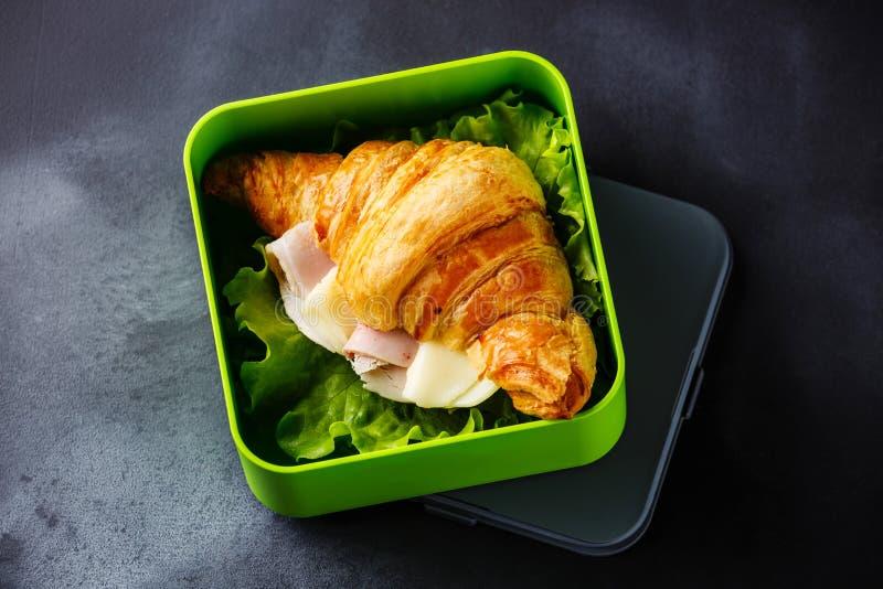 Sortez le sandwich à croissant de nourriture avec du fromage, le jambon et la laitue photo libre de droits