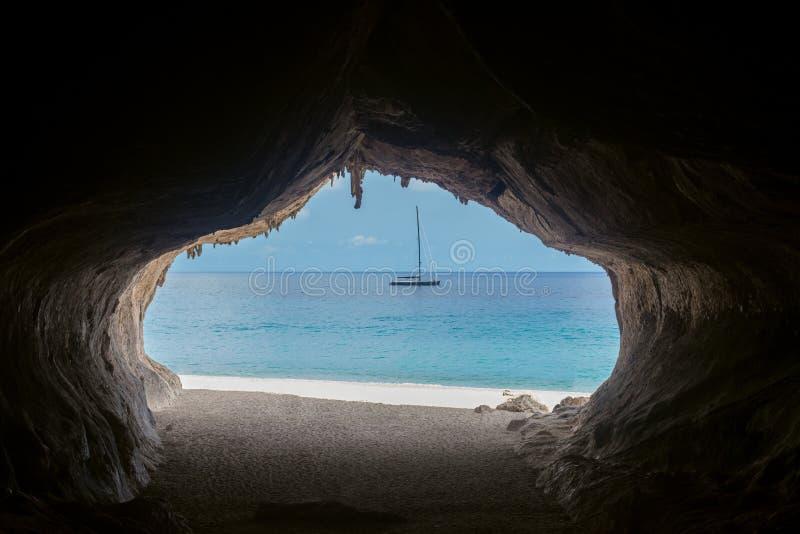 Sortie de la caverne donnant sur la beaux mer et bateau à la plage de Cala Luna photo libre de droits