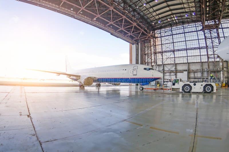 Sortie de virage des avions du hangar par un tracteur d'aérodrome, après la réparation photos stock