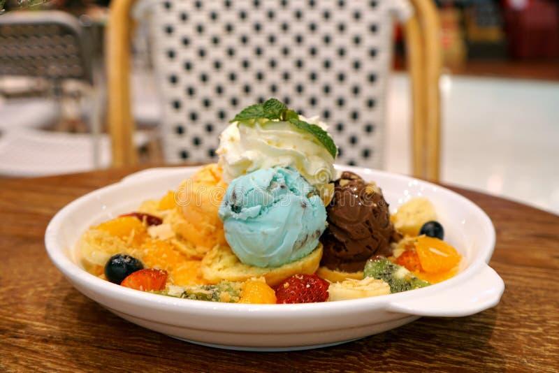 Sortierte Aromen schaufeln Eiscreme mit giwi, Erdbeere, Orange, Blaubeere, Bananenfrucht und der Spitze der Kleiderpeitschencreme stockbilder