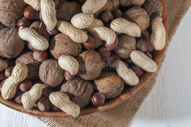 Sortierte Erdnüsse, Walnüsse und Haselnüsse Nüsse in einer Schüssel auf Leinwand Weißer hölzerner Hintergrund Nahaufnahme stockbilder
