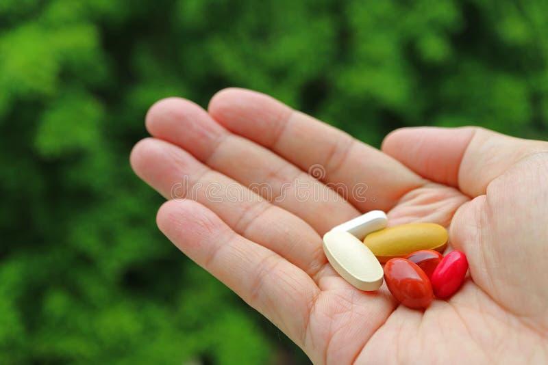 Sortierte Ergänzungs-Pillen in der Palme des Mannes mit undeutlichem grünem Laub im Hintergrund stockfotos