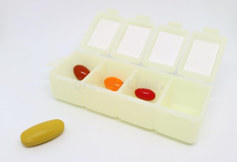 Sortierte Ergänzungs-Pillen im täglichen Pillen-Organisator Case mit einem von ihnen an der Außenseite lizenzfreies stockfoto