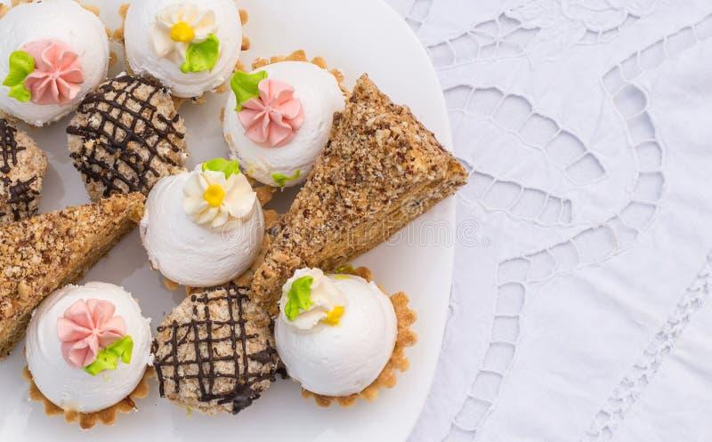 Sortierte fantastische feinschmeckerische kleine Kuchen auf einer Platte lizenzfreie stockfotografie