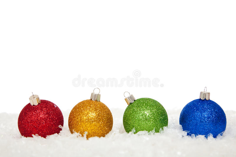 Sortierte farbige Weihnachtsverzierungen im Schnee stockfoto
