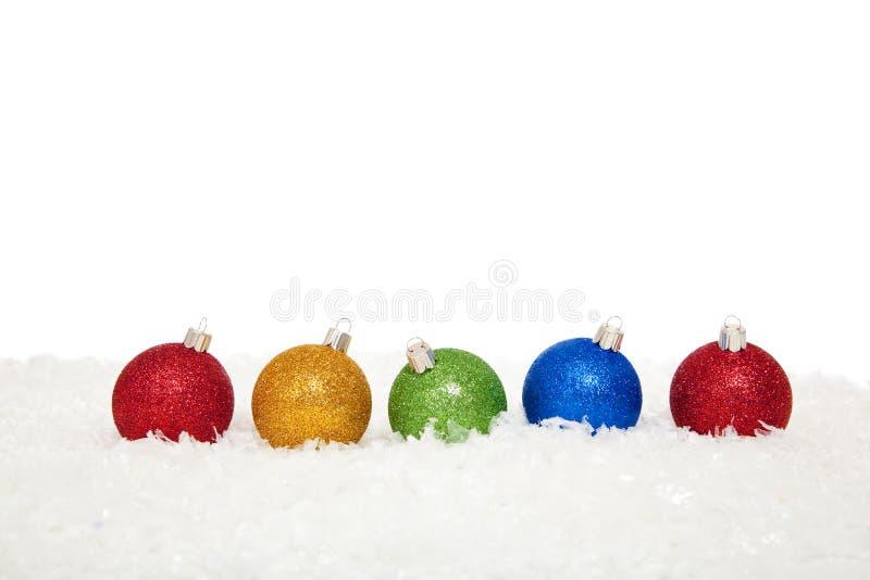 Sortierte farbige Weihnachtsverzierungen im Schnee lizenzfreie stockbilder