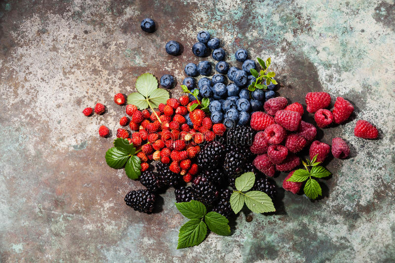 Sortierte frische Beeren mit Blättern stockbild