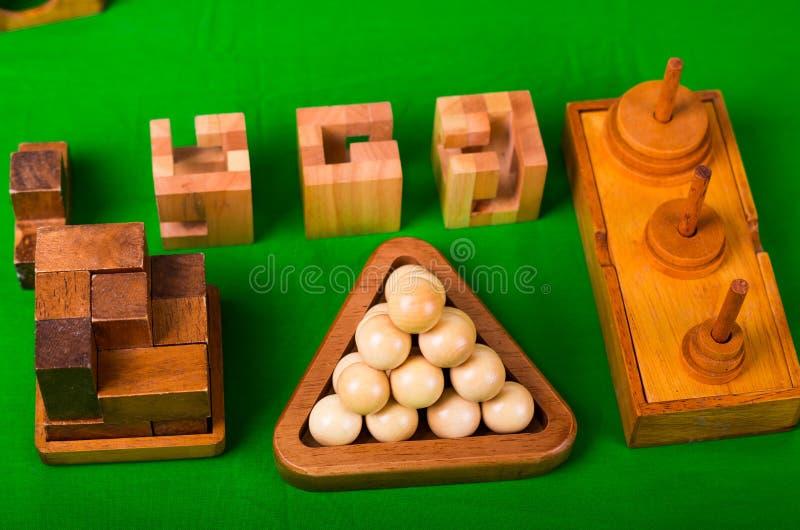 Sortierte hölzerne Gehirnharte nuss oder hölzerne Puzzlespiele auf grünem Hintergrund stockfoto
