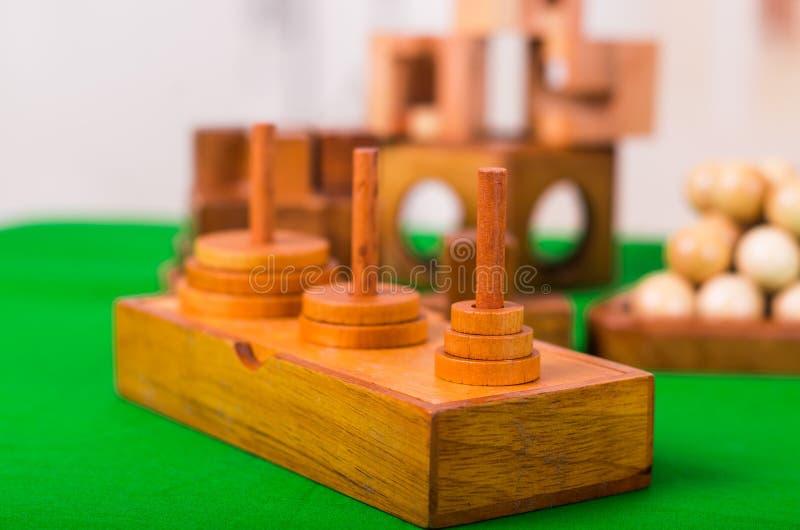 Sortierte hölzerne Gehirnharte nuss oder hölzerne Puzzlespiele auf grüner Tabelle in einem unscharfen Hintergrund lizenzfreies stockbild
