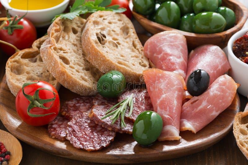 Sortierte italienische Antipasti - Feinkostgeschäftfleisch, -oliven und -brot stockbilder