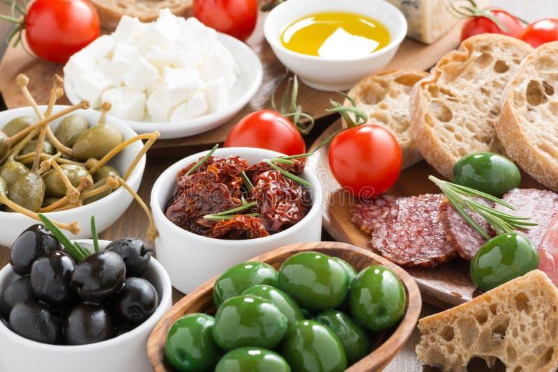 Sortierte italienische Antipasti - Oliven, Salami, Essiggurken und Brot lizenzfreies stockbild