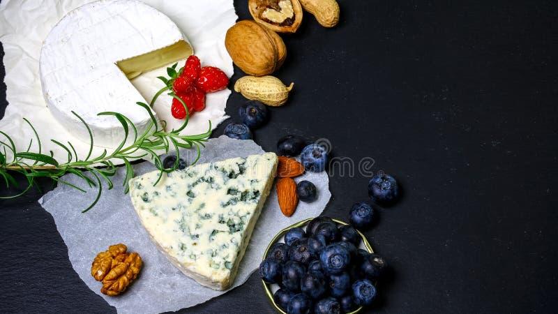Sortierte Käse auf Schieferbrett Camembert, Käse mit blauem Mehltau, Blaubeere, Erdbeeren, Nüsse Lebensmittelfahne für Text oder  lizenzfreies stockfoto