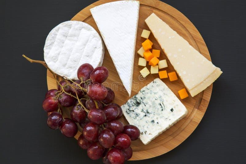 Sortierte Käse mit Trauben auf rundem hölzernem Brett auf dunklem Hintergrund Lebensmittel für romantisches stockbilder
