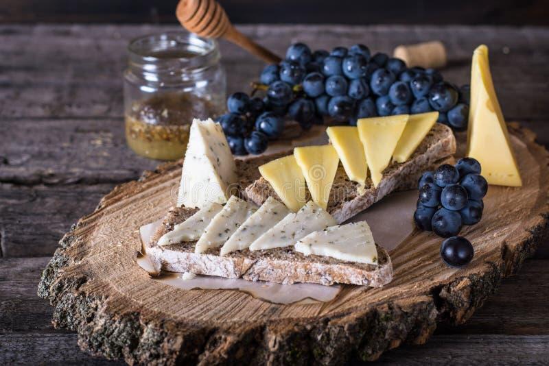 Sortierte Käse mit Trauben, Brot, Honig Ziegenkäse Hölzernes Brett Italienischer Aperitif Bruschetta Tasse Kaffee und Spiegelei lizenzfreie stockbilder