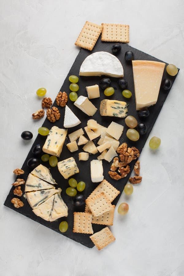 Sortierte Käse mit weißen Trauben, Walnüsse, Cracker und auf einem Steinbrett Lebensmittel für ein romantisches Datum an einem he stockbild