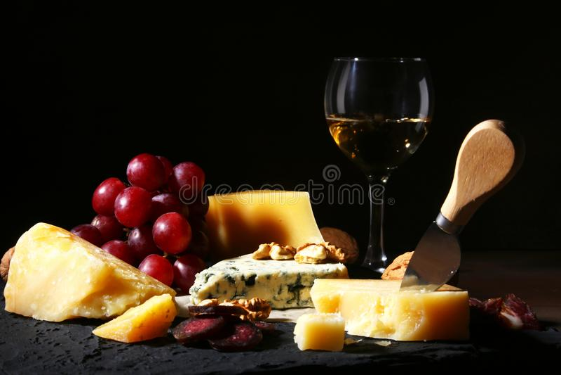 Sortierte Käse, Nüsse, Trauben, Früchte, geräuchertes Fleisch und ein Glas Wein auf einer dienenden Tabelle Dunkle und schwermüti stockfotografie