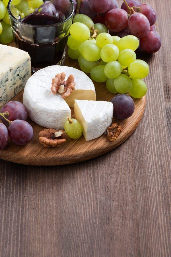 Sortierte Käse und frische Trauben auf dem Brett stockfoto