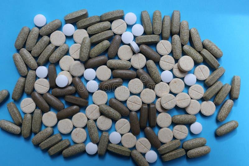 Sortierte Medizinpillen, -tabletten und -kapseln auf blauem Hintergrund stockbilder