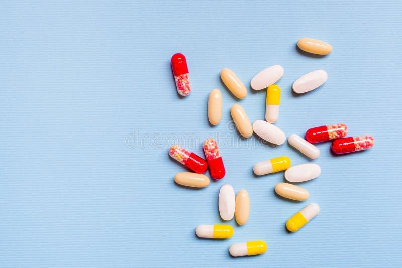 Sortierte pharmazeutische Medizinpillen, -tabletten und -kapseln über blauem Hintergrund lizenzfreies stockbild