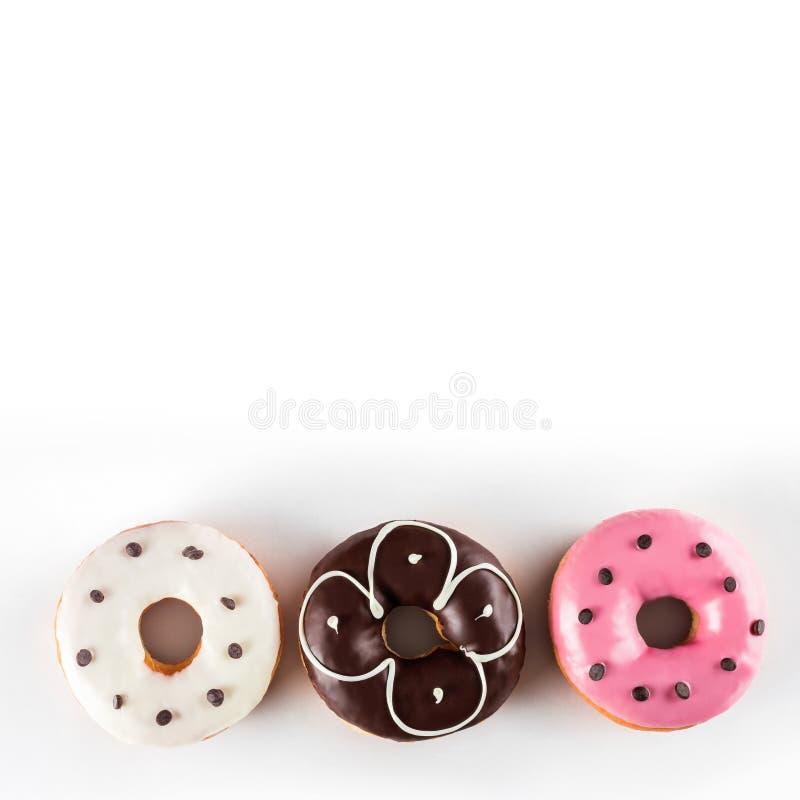 Sortierte Schaumgummiringe mit der Schokolade bereift und rosa glasiert lokalisiert auf weißem Hintergrund, Draufsicht lizenzfreie stockfotos
