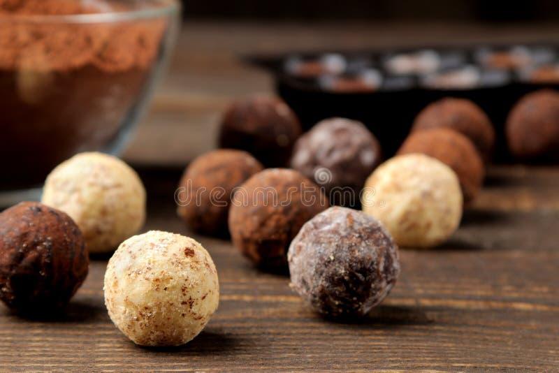 Sortierte Schokoladen Süßigkeitsbälle von verschiedenen Arten der Schokolade auf einem braunen Holztisch Nahaufnahme lizenzfreie stockbilder