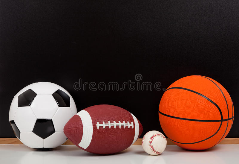 Sortierte Sportkugeln mit einem Kreidevorstand stockbild