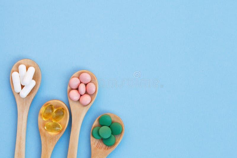 Sortierte verschiedene Medizinpillen, -tabletten und -kapseln im hölzernen Löffel lokalisiert auf blauem Hintergrund lizenzfreies stockbild