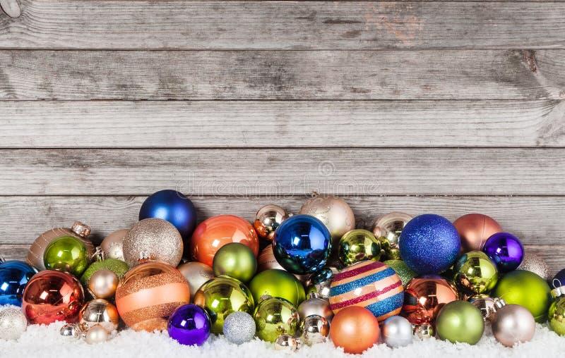 Sortierte Weihnachtsball-Dekorationen auf Schnee stockbild