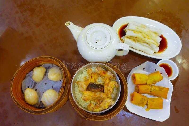 Sortierter chinesischer Lebensmittelsatz, Mehlklöße und Reisnudelrollen, berühmte chinesische Kücheteller auf einem Holztisch, Dr stockbild