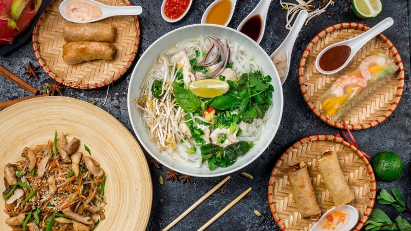 Sortiertes asiatisches Abendessen, vietnamesisches Lebensmittel Pho GA, pho BO, Nudeln, Frühlingsrollen stockfotos