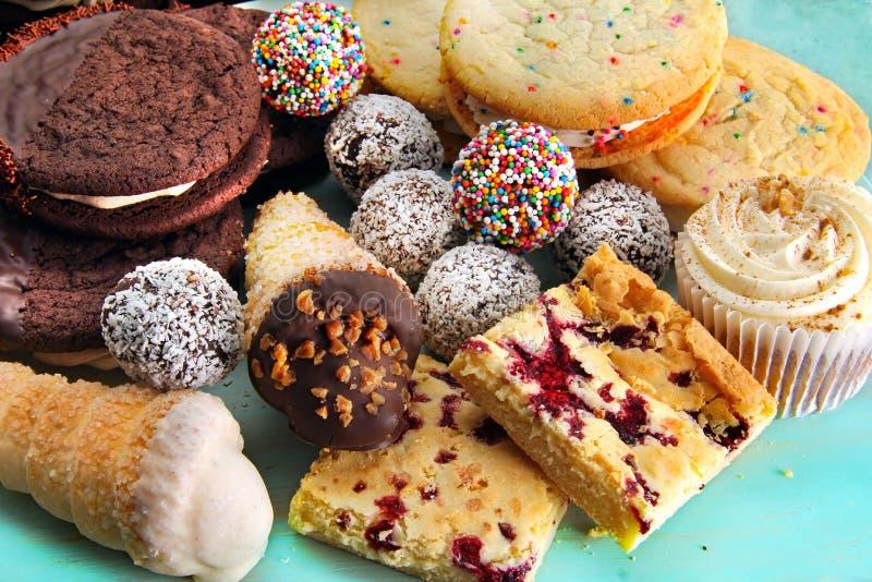 Sortiment av bakade söta fester, inklusive chokladrombollar, vaniljkakor, hallonfyrkanter och en muffin med lönnisläggning royaltyfria bilder