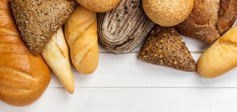 Sortiment av bakat bröd på trätabellbakgrund baner för annonsering och designen, bästa sikt för promo med kopieringsutrymme royaltyfria bilder