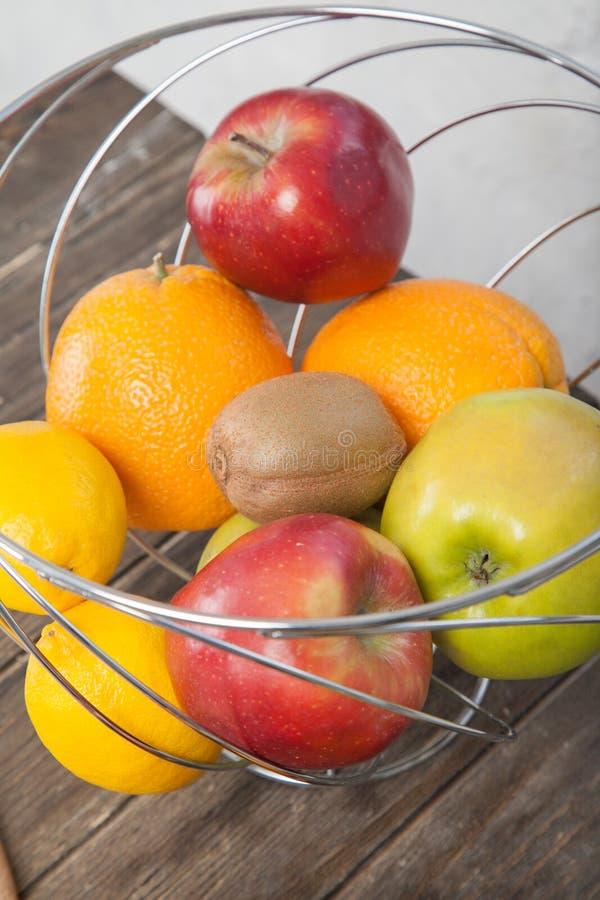 Sortiment av den exotiska fruktnärbilden: kiwi, rött och grönt äpple, apelsiner och citron på trätabellen royaltyfri fotografi