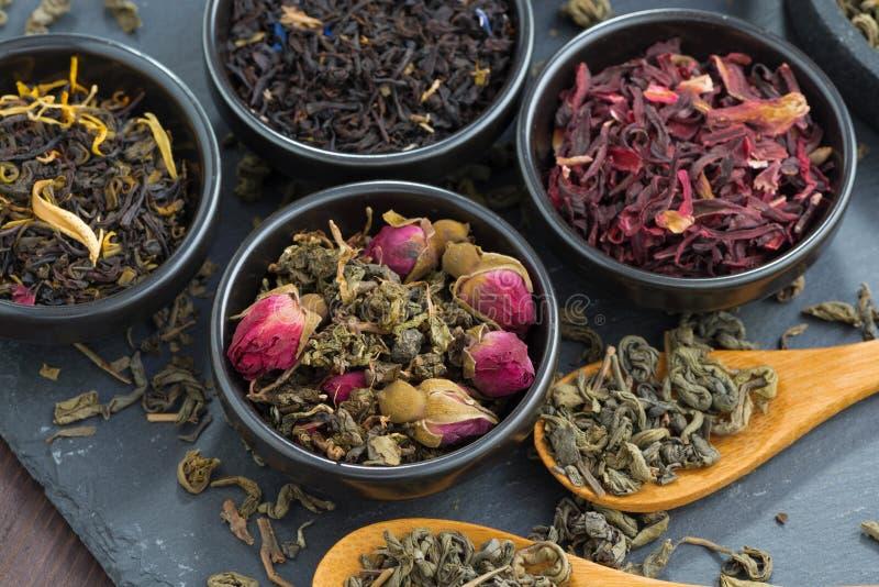 Sortiment av doftande torrt te i keramiska bunkar, bästa sikt royaltyfria bilder