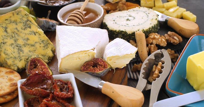 Sortiment av fransk och brittisk ost med fikonträd och valnötter royaltyfria foton