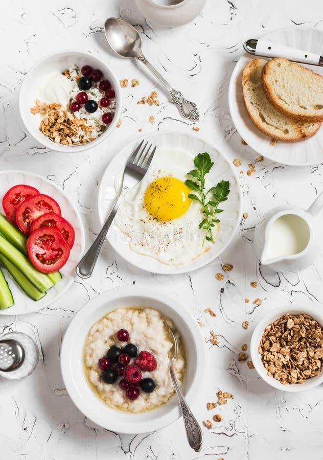 Sortiment av frukosten - stekt ägg, nya grönsaker, havremjöl med bär, keso, yoghurt och bär, hemlagad granola royaltyfri fotografi