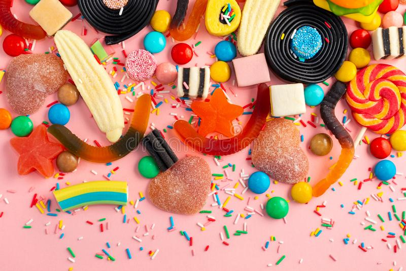 sortiment av klubbor, fruktkonfekten, godisar och stänk på rosa färger som bakgrund, kopieringsutrymme royaltyfri foto