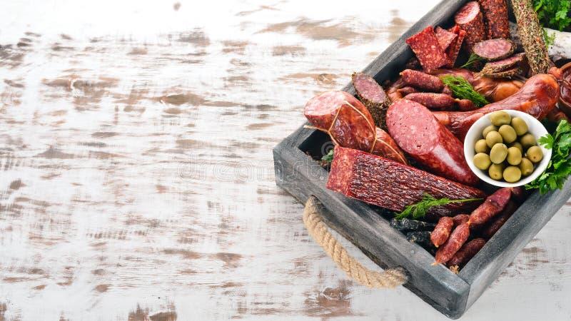 Sortiment av korvar och mellanmål i en träask Korv Fuet, salami, paperoni P? en vit tr?bakgrund royaltyfria bilder