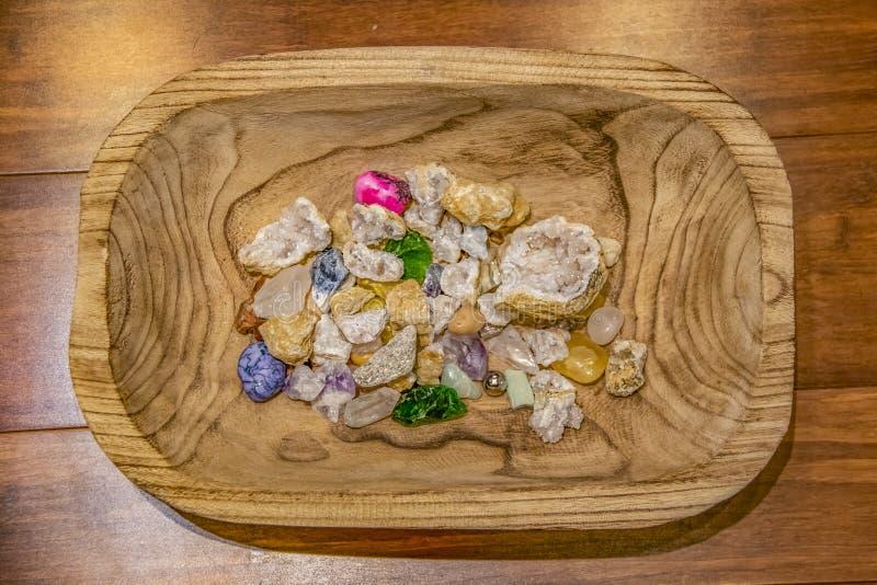 Sortiment av kristaller och stenar av olika färger och texturer i ett snidit träbunkesammanträde på en wood plankayttersida - öve royaltyfri foto