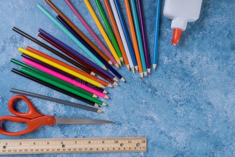 Sortiment av kulöra blyertspennor, linjalen, lim och sax royaltyfria bilder