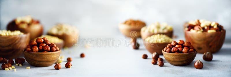 Sortiment av muttrar i träbunkar Kasjun hasselnötter, valnötter, pistaschen, pecannötter, sörjer muttrar, jordnöten, russin (Ris, royaltyfri fotografi