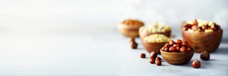 Sortiment av muttrar i träbunkar Kasjun hasselnötter, valnötter, pistaschen, pecannötter, sörjer muttrar, jordnöten, russin (Ris, royaltyfri bild