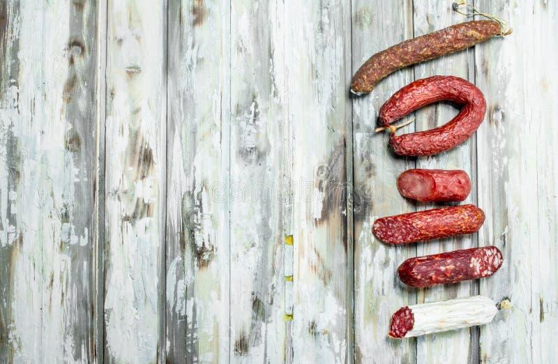 Sortiment av olik rökt salami med örter och smaktillsatser royaltyfria foton