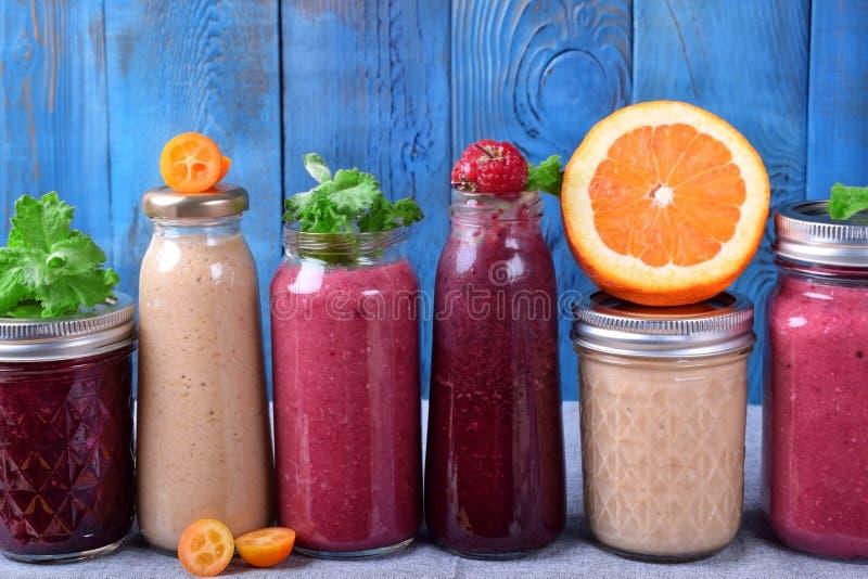 Sortiment av olika smoothies som överträffas med frukter, bär och mintkaramellen på tabellen arkivfoto