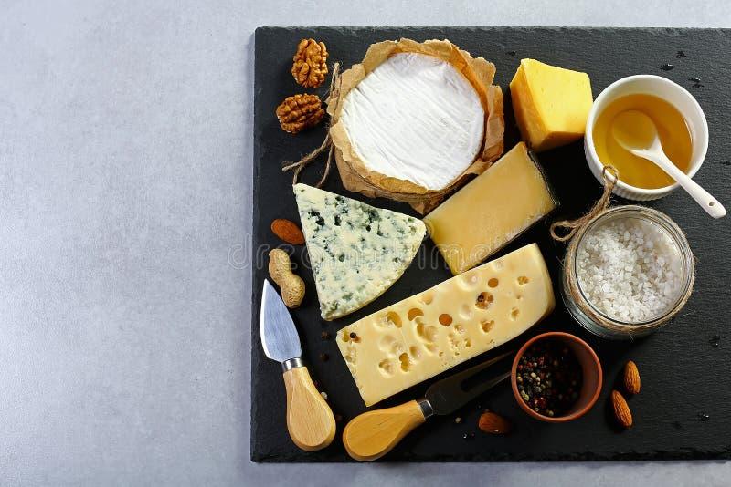 Sortiment av ost med honung, muttrar och kryddor på en stenplatta Ostportionkniv close upp Uppsättning arkivfoto